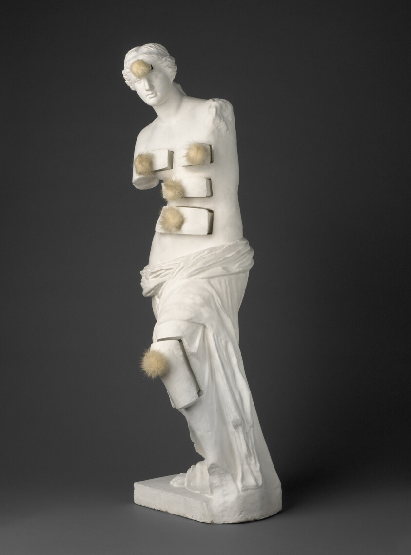 Venus de Milo with Drawersby Salvador Dalí: A photographofa half-size plaster reproduction of the famous marble statue of Venus de Milo, altered with pompon-decorated drawers in the figure's forehead, breasts, stomach, abdomen, and left knee.